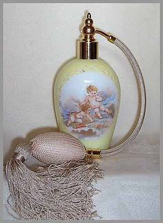 """This vintage perfume atomizer stands 6"""" tall. The color is Pale Yellow. On the front of the bottle there are two Putti, one reaching for an arrow. The background shows a Blue sky and soft fluffy clouds. This perfume atomizer is beautiful and so romantic, and is in excellent condition"""