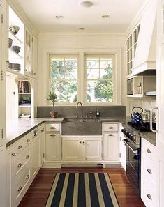 Shelves in front of transom windows allows for light filled storage in a small kitchen