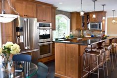 Large open counter space- could be accomplished by removing upper cabinetry and making counter top one level- nice pendant lights