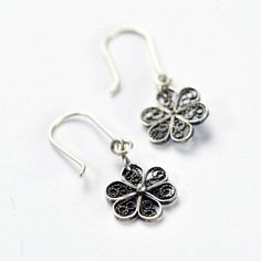 Unique handmade filigree earrings with a filigree ball on the top and a silver flower on the bottom.