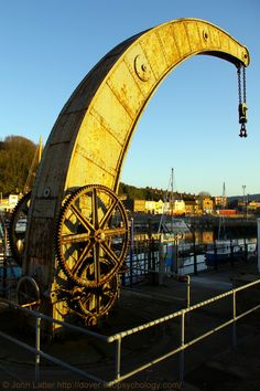 The Victorian Fairbairn Crane of Esplanade Quay at Sunrise, Dover Marina, Kent, England, UK. Built in 1868, this is a later example of a revolutionary design by Sir William Fairbairn shown at the 1851 Crystal Palace Great Exhibition of London. A Listed Building described as a hand-driven rotary crane with tubular swan-neck jib. Background: Wellington Dock, Western Heights, and Snargate Street. Industrial Archaeology (Archeology), Travel and Tourism. See…