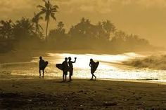 Surfers in Bali, about to catch the first waves at 6am.