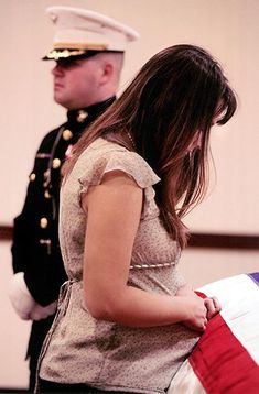 Katherine Cathey presses her pregnant belly on the coffin of her husband Marine 2nd. Lt. Jim Cathey, who was serving overseas