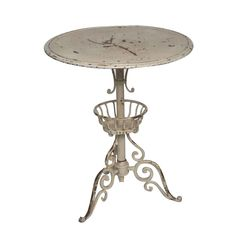 Adele Cream Side Table at Found Vintage Rentals. Cream metal pedestal side table with scrolled details. 24 inches in diameter.
