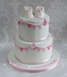 Buttons and bunting two tier girl's christening cake with sugar baby bootees