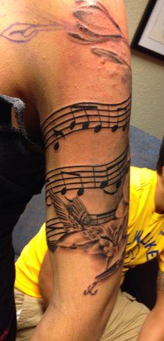 Female half sleeve music flower tattoo