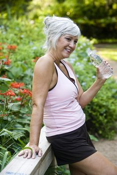Mature woman in her 50s in workout clothes drinking a bottle of water, standing on wooden bridge in park  #50s #clothes #drinking #female #fitness #lifestyle #mature #midlife #woman