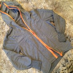 """Zipper sweatshirt This awesome take on a sweatshirt grabs your eye with it's multiple neon orange zippers and several ways to zip it. Hooded. Length: 22"""", bust: 18"""", sleeve length: 22.5"""", no size tag, please see measurements. Tops Sweatshirts & Hoodies"""