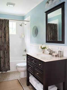 Blue-and-Brown Bath Light blue walls set the stage for a trendy brown-and-blue color scheme that showcases an espresso-stained vanity and a romantic brown paisley shower curtain. The dark browns are balanced by a white subway-tile shower surround and beaded-board wainscoting atop a basket-weave tiled floor in taupe, brown, and white. Silvertone fixtures and hardware add a subtle gleam to the mix.