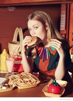 Zanna eats a hamburger while modeling colorful Marni dress and Del Duca necklace.