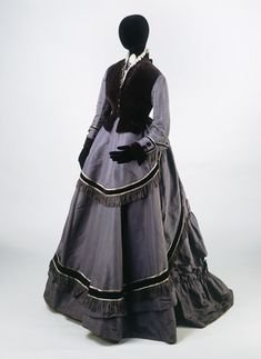 """Grey silk taffeta and velvet ensemble (front view), 1868-70. Ensemble consisting of a bodice, skirt and sleeveless jacket. Said to have been worn by a """"city merchant's wife""""."""