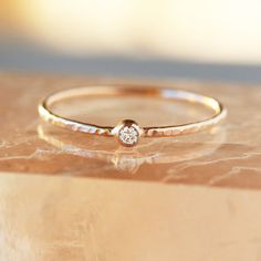 • Tiny Diamond Stacking Ring in either 14k Yellow Gold or 14k Rose Gold • CanadaMark diamond 2mm in diameter, approximately .03 carats, G/H color, SI2-SI3 clarity • Hammered 1mm band made of recycled gold • Model photo shows the ring on a size 8 finger • One week processing time A