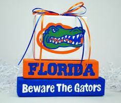 University of Florida Gators Sport WoodenBlock Shelf Sitter Stack measures 7 wide x tall. Perfect for your home, man cave, or office decor! Florida Girl, Florida Gators, Football Door Hangers, Football Crafts, University Of Florida, Wooden Blocks, Ribbon Colors, Craft Fairs, Office Decor