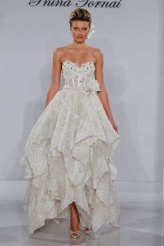 Pnina Tornai. This tea length gown features a sweetheart neckline with a basque waist in lace and beaded embroidery