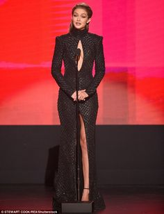 Beaming beauty: Gigi showed a hint of cleavage in the shimmering piece, which featured a turtleneck-style neckline, long-sleeves and a large slit in the skirt