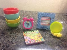 look for miniature items at michaels - calendar is a keychain, but remove the chain, and it's a wall calendar for dolls. Mini alarm clock really works. Small jar held binder clips, but works in a doll kitchen. Bowls are from dollar section - prep bowls