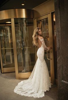 Glamorous open back long sleeve lace wedding dress with fit and flare shape.