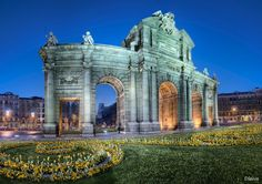 Spain, Madrid, Puerta de Alcalá illuminated at night by Domingo Leiva La Puerta de Alcalá is one of five former royal doors giving access to city of Madrid. Monumental gateway which is located next to Cibeles Fountain and Parque del Retiro.