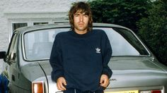 Liam Gallagher dressed in tracksuit bottoms and a matching hoodie in front of his Bristol car. Lennon Gallagher, Liam Gallagher Oasis, Gene Gallagher, Liam Oasis, Bristol Cars, Oasis Band, Liam And Noel, El Rock And Roll, Beady Eye