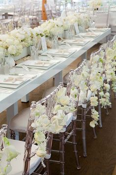 Clear Chiavari chairs are decorated with garlands of roses, orchids and crystals. Colin Cowie Weddings