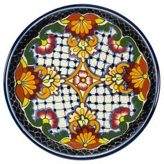 Handmade talavera plates are used for dining and decorating kitchen walls. A red, black, yellow and white plate from Mexico is microwave safe. by Rustica House #myRustica