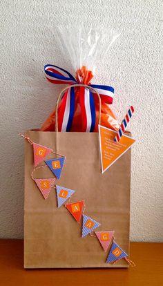Geslaagd: Rood, wit, blauw, oranje. Bruine papieren draagtas/kadotas versierd met slingers gemaakt met papier en lint. Knijper is beplakt met washi tape.