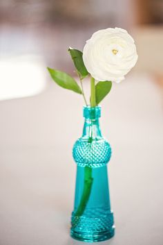 For a relaxed, old-fashioned look, swap traditional single-stem bud vases for mismatched glass bottles. {Riverland Studios}