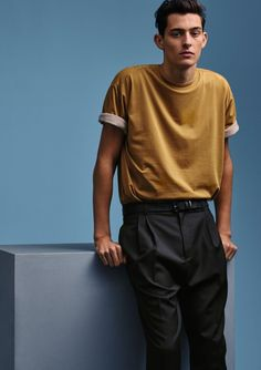 Rhys Pickering sports a t-shirt with rolled sleeves and front pleated trousers from H&M Studio.