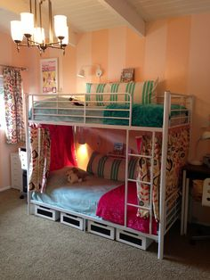 Bunk beds finished! Inexpensive metal white bunk bed cozied up with curtains. Desks for each girl on side. Reading lamp, ikea spice rack bookshelf. Chalkboard underbed rolling storage.
