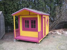 A yellow and pink wooden playhouse.