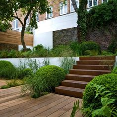 very small urban garden in Kensington by Landform Consultants using wood decking, corten stairs, exposed brick for texture & shape, green garden to soften