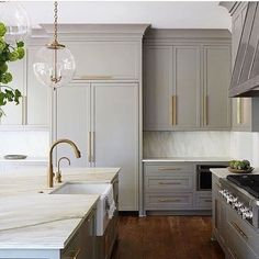 Beautiful kitchen design featuring light gray cabinets, antiqued gold / brass hardware, white and grey granite countertops and backsplash, a large island with a deep farm sink, and glass globe pendant lights - Vintage Modern Kitchen Ideas & Decor