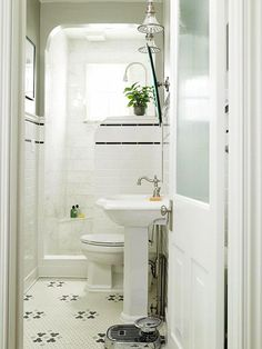 this is one of my all time favorite small bathrooms.  black and white mosaic floor tile, frosted glass door, and classic pedestal sink.  no shower curtain needed.