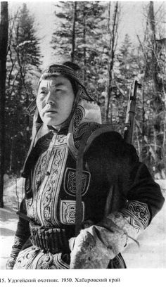 Here is a Udege man in full winter attire; embroidered coat, a hood with seperate earmuffs and covered by a cap.