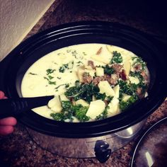 Zuppa Toscana · Best Italian soup EVER!  Crock pot recipe! Directions:  1: Brown Italian sausage and one strip of bacon, drain and add to crock pot 2. Chop up half of an onion and about 1 tablespoon of fresh chopped garlic clove 3. Pull apart about 3 cups of kale 4. Cut up 1 large potato 5. Add 3 cups of chicken broth 6. Add 2 cups of chicken broth and 2 cups of hot water 7. Put in garlic salt, pepper and 1tbs of butter 8. Cook 3 hours on high and 1 hour on low!
