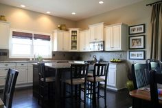 Example of BM Grant Beige in kitchen with black stools and white cabinets