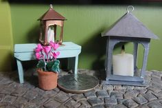 Two dollhouse scale candle lanterns made from photo paper.