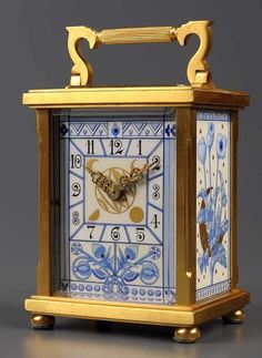 A gilt brass carriage clock, c.1900, with ornate Art Nouveau style porcelain arabic dial centred by gilt phases of the moon, within foliate and geometric border, the side panels with moon and sunburst designs with flowers and insects, platform lever escapement, striking on a gong, shaped rectangular case, on ball feet, 5in. high #antiquehour #clocks @UKauctioneers.com.com.com.com