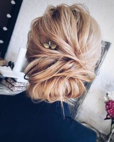 a casual twisted updo with a double chignon and a rhinestone hairpiece for an accent
