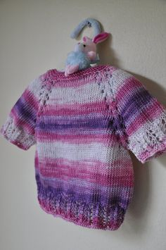 This is a hand knitted baby vest.  -Made out of wool yarn.  -Three pink buttons with ladybugs.  -Fits for 6-12 months.  -Length is 25 cm / 9.8