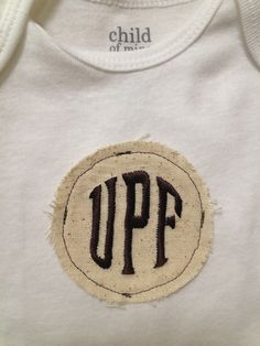 Monogram on a burlap type muslin/fabric, then sew it on a shirt or onesie. You can use a peel & stick or iron on adhesive to keep it in place before sewing. The edges will fray more when washed. How cute!