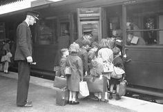 Schoolchildren board a special train at a London station as they are evacuated to the west country to escape the Nazi bombing, June 13, 1940. All the children wear identity labels and carry their gas masks.