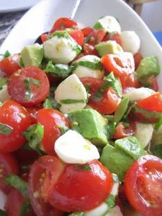 Ingredients: 1 container cherry tomatoes, cut in half or quartered if large 1 carton fresh mozzarella cheese pearls, drained (cut in half if desired) 1 avocado, peeled and diced 1/3 cup basil, julienned 2 tablespoons fresh parsley 1/4 cup lemon juice 1/4 cup olive oil salt and pepper to taste Baguette - optional