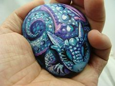 A small baby Dragon hand painted on a stone.