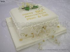 Square ivory coloured 50th wedding anniversary cake topped with a spray of ivory roses with gold beaded wire. Gold message text, hearts and swirl chiffon ribbon, and tied with a large bow