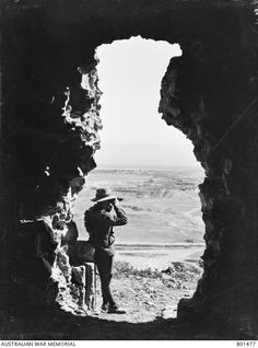 The Jordan Valley, with Jericho in the middle distance, seen through a shell hole in an old tomb. A soldier is looking through binoculars into the distance. Hurley, James Francis (Frank): Ottoman Empire: Palestine, 1 March 1918