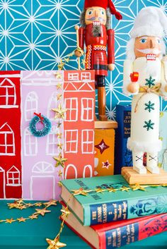 A painted Christmas village is all you need to bring a dose of seasonal cheer (and colour!) to your Christmas mantel, sideboard, or console table! Grab your Americana Acrylic Paints & Dazzling Metallics to get started. #christmascraft #christmasvillage...