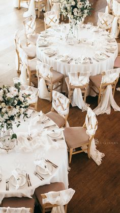 Classic indoor white and brown wedding reception with tall floral centerpieces   indoor wedding reception, indoor wedding decorations, indoor wedding dinner, simple indoor wedding, rustic indoor wedding, indoor wedding ideas, elegant indoor wedding, fall indoor wedding, indoor wedding themes, indoor wedding on a budget, indoor wedding photos, boho indoor wedding, romantic indoor wedding, DIY indoor wedding, white wedding reception, white wedding decorations, white wedding with greenery