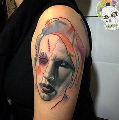 Marylin Manson portrait mashup tattoo on the left upper arm.