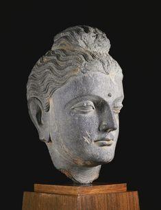 A GREY SCHIST HEAD OF BUDDHA Ancient region of Gandhara, Kushan period, 2nd/3rd century Height: 12 3/4 in. (32.4 cm)